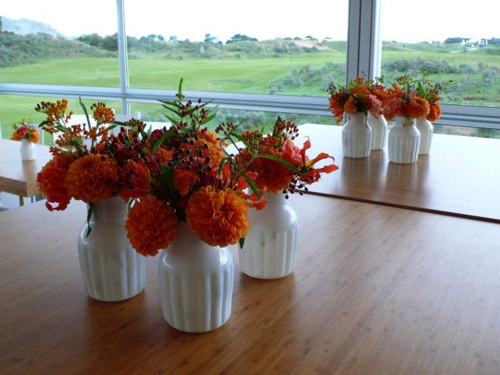 tafeldecoratie oranje bloemen in witte vaasjes dahlia