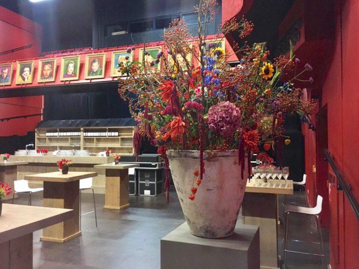 Grote aardewerk pot met warme gekleurde bloemen