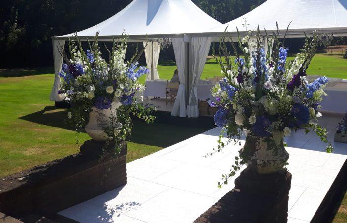 Bloemdecoratie in robuuste aardewerkenpot in blauwe en witte tinten tijdens een doopfeest