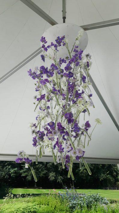 Hangende bloemdecoratie in blauwe en witte tinten tijdens een doopfeest