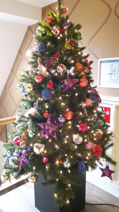 Kerstboom met gekleurde kerstdecoratie bij restaurant Loetje