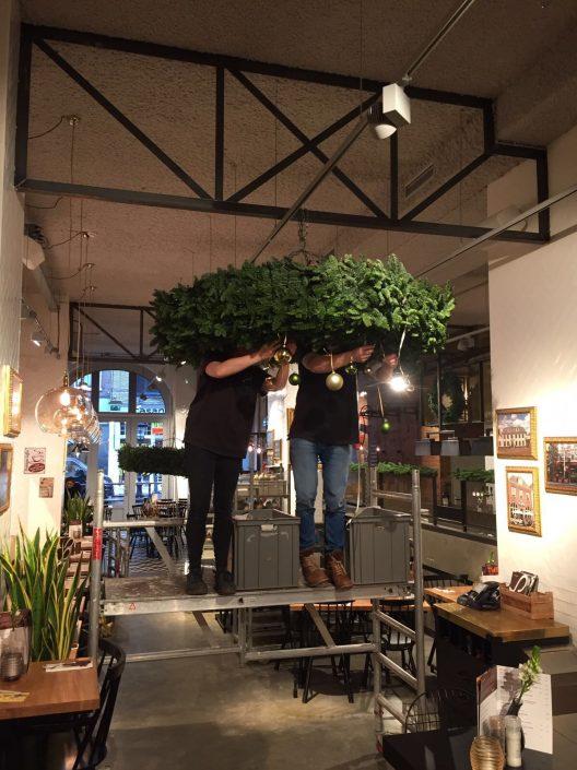 Kerstkrans wordt opgehangen bij restaurant Loetje